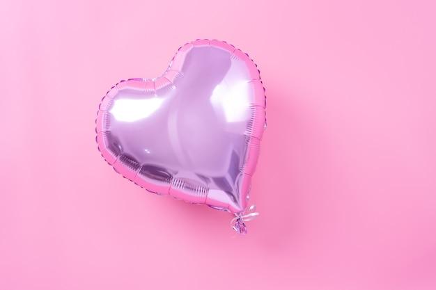Valentijnsdag minimaal ontwerpconcept - mooie echte hartvorm folieballon geïsoleerd op lichtroze achtergrond