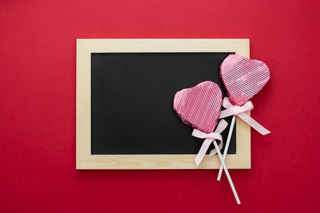 Valentijnsdag mock up, lege schoolbord met lolly in de vorm van een hart en glitter geïsoleerd op rode achtergrond, kopie ruimte.