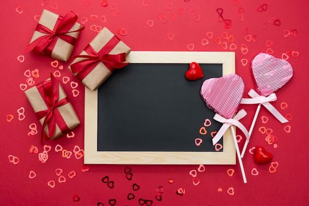 Valentijnsdag mock up, schoolbord met lolly in de vorm van een hart, geschenkdozen en glitter geïsoleerd op rode achtergrond, kopie ruimte.