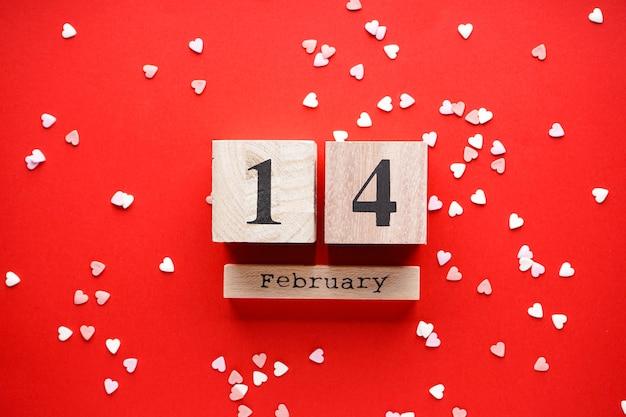 Valentijnsdag. moederdag achtergrond. liefde concept. zoete harten en houten kalender op een rode achtergrond, plat leggen.