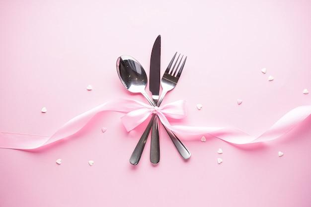 Valentijnsdag. moederdag achtergrond. liefde concept. zoete hartjes en bestek op een witte plaat met een roze lint op een roze achtergrond, plat leggen.