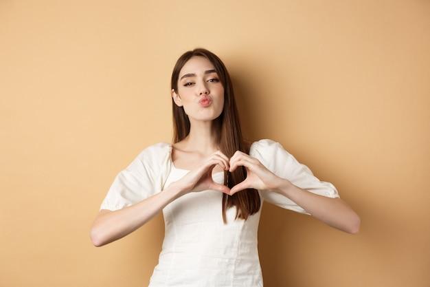 Valentijnsdag. mooie jonge womam in witte jurk, verliefd bekennen, lippen tuiten voor kus en hartgebaar tonen aan minnaar, staande op beige achtergrond.