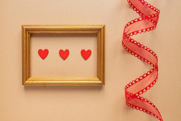 Valentijnsdag of bruiloft romantisch concept. gedraaid decoratief lint en gouden fotokader met rode harten op beige achtergrond.