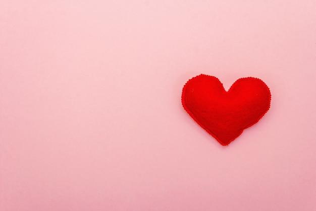 Valentijnsdag of bruiloft romantisch concept. rood hart op roze achtergrond, bovenaanzicht, kopie ruimte, plat leggen