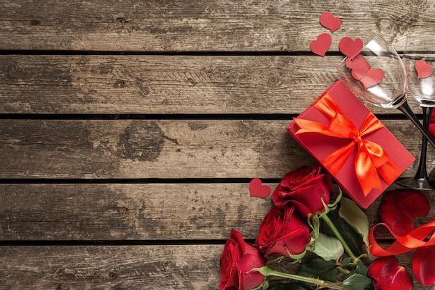 Valentijnsdag of moederdag rode geschenkdoos met bloemen papier harten en wijnglazen op houten achtergrond bovenaanzicht