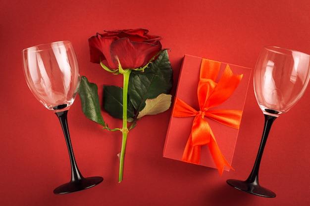 Valentijnsdag of moederdag rode geschenkdoos met bloemen steeg wijnglazen op rode achtergrond bovenaanzicht