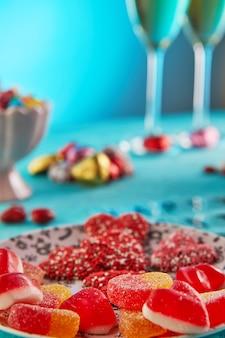 Valentijnsdag of romantisch diner met snoephartjes, glazen champagne en elegante tafelsetting en valentijnsdag belettering op een lichtblauwe tafel.