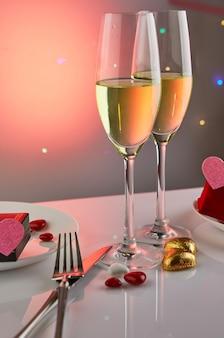 Valentijnsdag of romantisch verjaardagsdiner met snoephartjes, glazen champagne en elegante tafelsetting met reflectie en lampjes in de tafel.