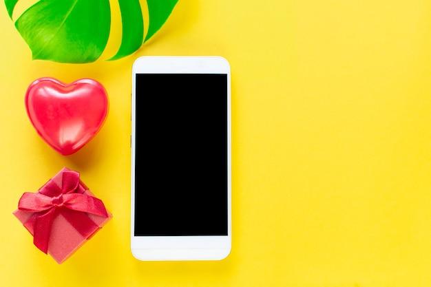 Valentijnsdag online winkelen. seizoensgebonden vakantie-uitverkoop. smartphone, rood hart, cadeau, monstera op gele trendachtergrond. romantisch winkelen voor gerls, vrouwendag, cadeaus kopen valentijnsdagliefhebbers