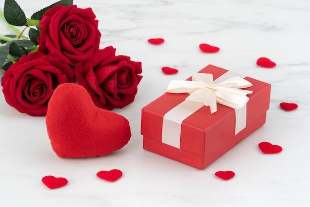 Valentijnsdag ontwerp concept achtergrond met roze bloem en geschenkdoos op marmeren witte achtergrond