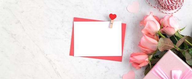 Valentijnsdag ontwerp concept achtergrond met roze roze bloem en geschenkdoos op marmeren witte achtergrond