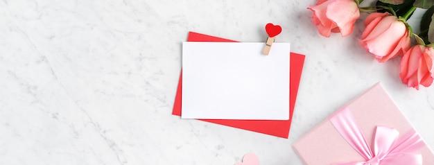 Valentijnsdag ontwerp concept achtergrond met roze roze bloem, geschenkdoos en kaart op marmeren witte achtergrond