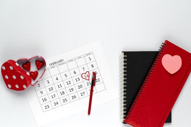 Valentijnsdag op kantoor. hartvormige doos chocolaatjes, februari-kalender en notitieboekjes op een witte tafel.