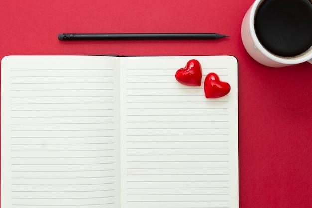 Valentijnsdag. open notitieboekje met rode harten en een potlood, op rode achtergrond, exemplaarruimte voor tekst.
