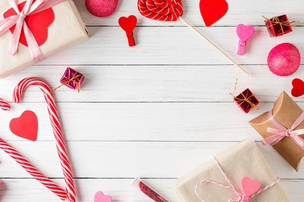 Valentijnsdag oppervlak. frame van rode harten, geschenkdoos met lint en snoep snoep op een witte houten oppervlak, bovenaanzicht