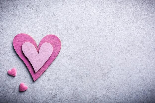 Valentijnsdag oppervlak met decoratief roze houten hart op betonnen steen met kopie ruimte voor tekst. valentijnsdag concept. uitzicht van boven