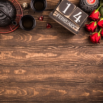 Valentijnsdag oppervlak met groene thee, zwarte theepot, kaarsen, rozen en houten kalender. valentijnsdag concept. bovenaanzicht. kopieer ruimte