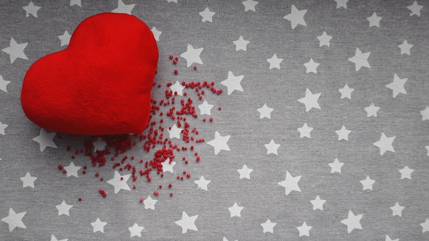 Valentijnsdag oppervlak met zacht stuk speelgoed hart op een grijze ondergrond met witte sterren. bovenaanzicht. voor banner, kaartenontwerp
