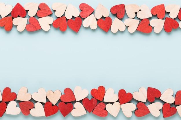 Valentijnsdag pastel snoep harten op blauwe wenskaart.
