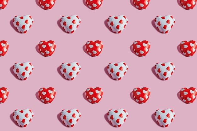 Valentijnsdag patroon met snoep hartjes op roze