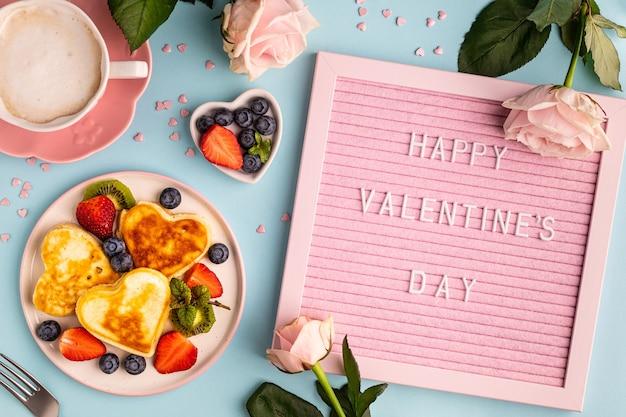 Valentijnsdag plat lag met hartvormige pannenkoeken op een blauw. valentijnsdag concept. uitzicht van boven.