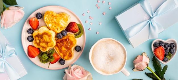 Valentijnsdag plat lag met hartvormige pannenkoeken op een blauw.