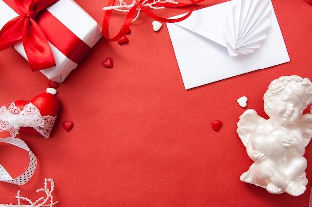 Valentijnsdag plat lag op een rode achtergrond. envelop, geschenk, hart, engel, linten. .