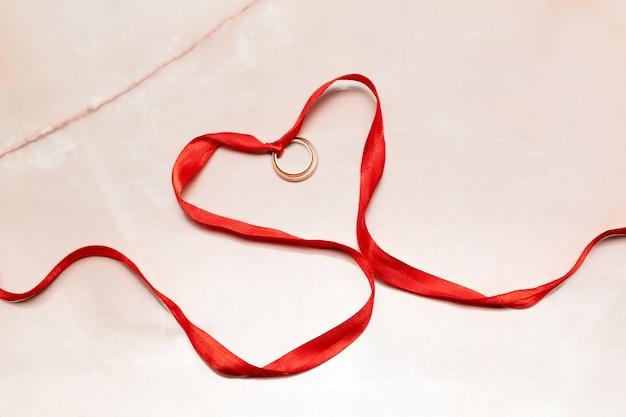 Valentijnsdag plat lag rood hart van lint en gouden trouwringen op roze papier.
