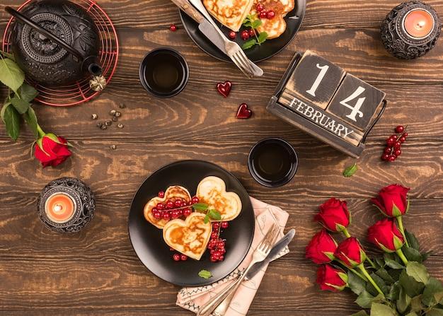Valentijnsdag plat met heerlijke pannenkoeken in de vorm van hart, groene thee, zwarte theepot, kaarsen en rozen. valentijnsdag concept wenskaart. bovenaanzicht