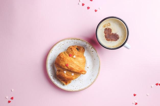 Valentijnsdag plat met twee kopjes koffie, croissant op plaat op roze