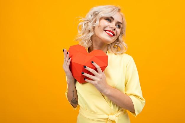 Valentijnsdag . portret van een gelukkig blond meisje met make-up met een rood hart gemaakt van papier op een geel met copyspace