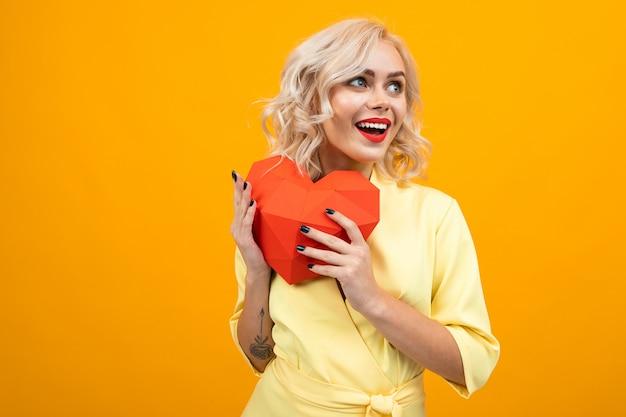 Valentijnsdag . portret van een gelukkig blond meisje met make-up met rode lippenstift met een rood hart gemaakt van papier op een geel met copyspace