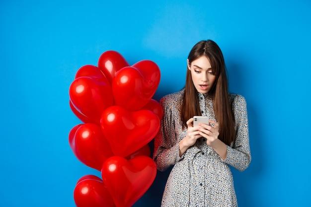Valentijnsdag. portret van een jonge vrouw die in de buurt van rode romantische ballonnen staat, verbaasd naar het smartphonescherm kijkt, blauwe achtergrond