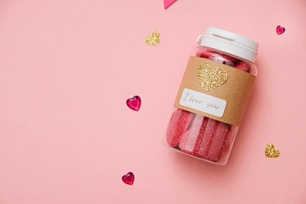 Valentijnsdag: pot met zoete geleivruchten en harten op roze achtergrond
