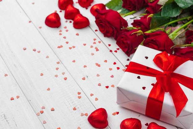 Valentijnsdag. rode rozen en geschenkdoos op houten tafel