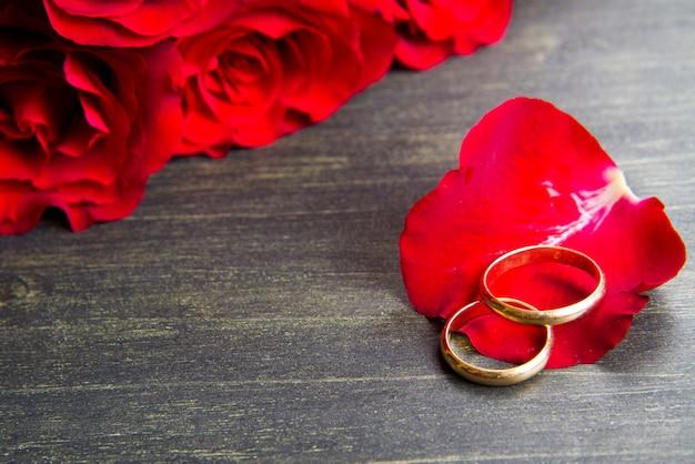 Valentijnsdag rode rozen en trouwring een houten achtergrond