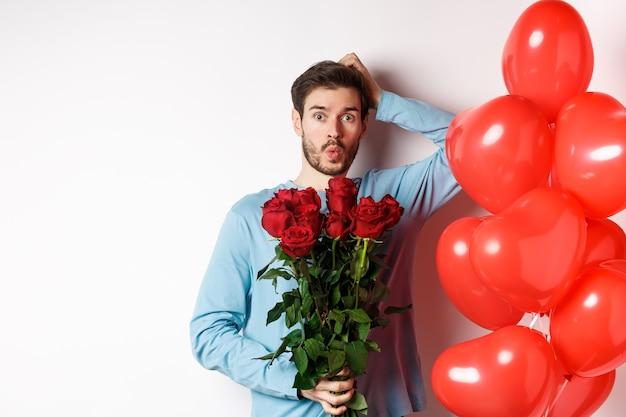 Valentijnsdag romantiek. bezorgd vriendje houden boeket van rode rozen en rood hart ballonnen, hoofd krabben en angstig op zoek, romantische date op wit gaande