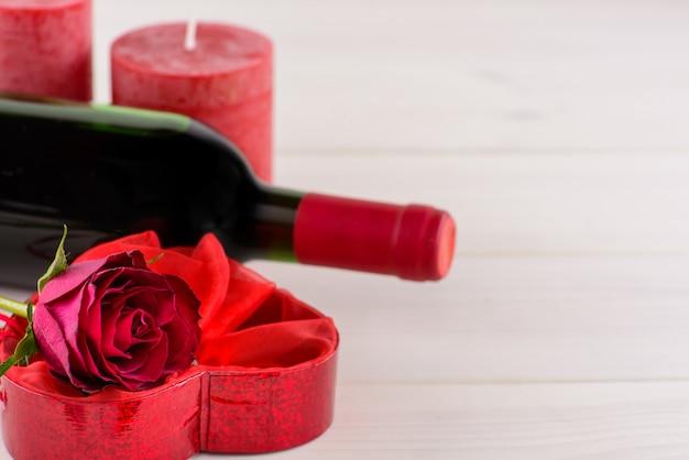 Valentijnsdag romantische achtergrond met rode roos en wijn.
