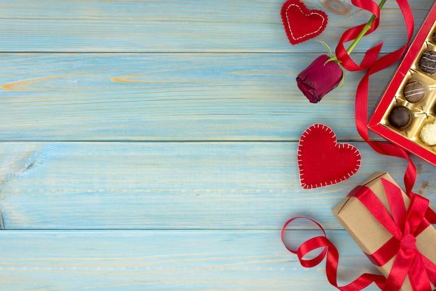 Valentijnsdag romantische decoratie met rozen en chocolade op een blauwe houten tafel.