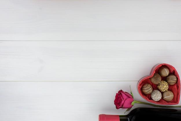 Valentijnsdag romantische decoratie met rozen, wijn en chocolade op een witte houten tafel.