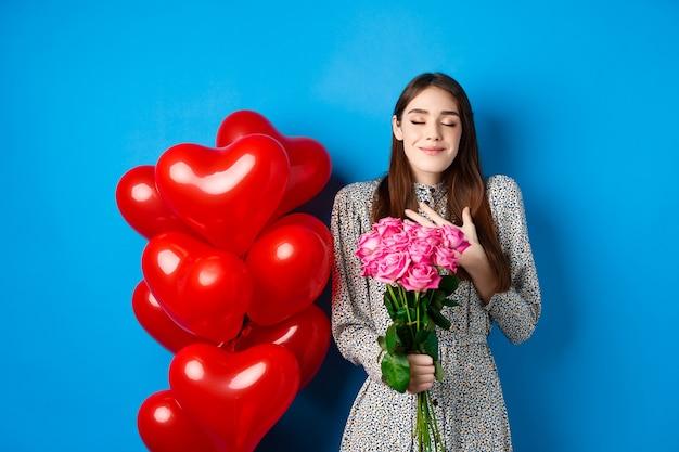 Valentijnsdag. romantische mooie vrouw in jurk, ogen dicht en glimlachen, bloemen ontvangen van minnaar, ruikend boeket roze rozen, blauwe achtergrond
