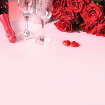 Valentijnsdag romantische set voor twee, boeket van rode roos, cadeau, harten chocolade snoepjes, champagne op roze. wenskaart met kopie ruimte.