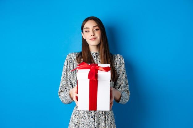 Valentijnsdag romantische vriendin brengt cadeau en glimlach naar camera in trendy jurk op blauwe b...