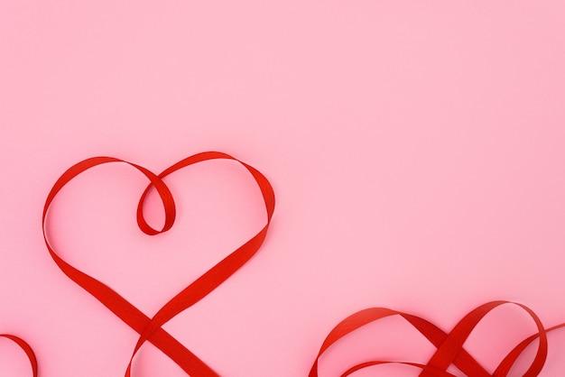 Valentijnsdag rood lint krommen in de vorm van een hart op een roze achtergrond. feestelijke achtergrond voor bruiloft en wenskaarten, mockup, kopie ruimte.