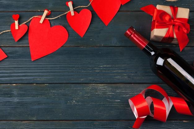 Valentijnsdag. rood roze bloemen, wijn en geschenkdoos op houten tafel.