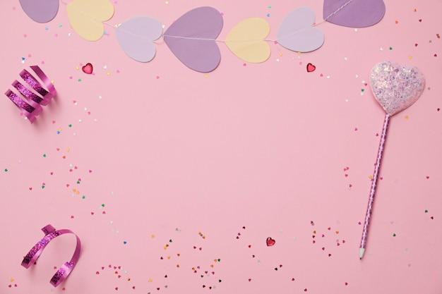 Valentijnsdag samenstelling: confetti, harten en pen op roze achtergrond