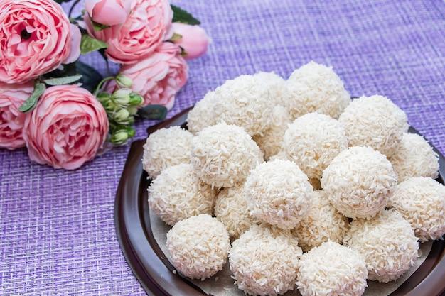Valentijnsdag samenstelling - kokossnoepjes en roze bloemen op een paarse achtergrond