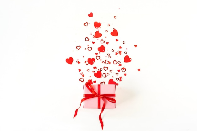 Valentijnsdag samenstelling met roze geschenkdoos en hartsymbool confetti op wit oppervlak