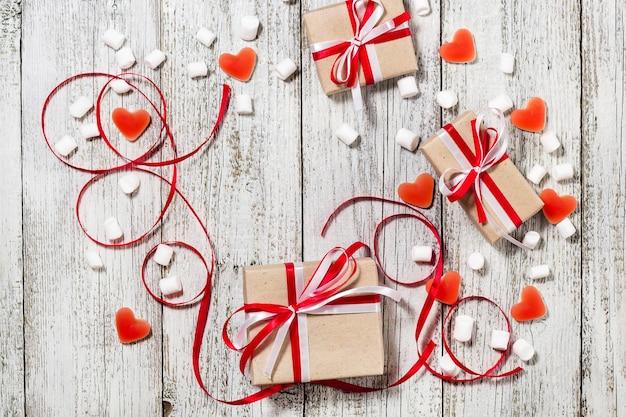 Valentijnsdag snoep harten marshmallows en doos met geschenken in kraft papier over witte houten tafel.