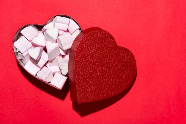 Valentijnsdag snoep harten marshmallows in vak op rode achtergrond